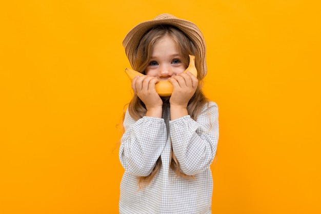 Charming girl child in a hat with a banana in his hand on a yellow background