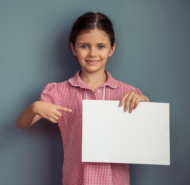 Charming girl in cute dress is holding blank sheet of paper