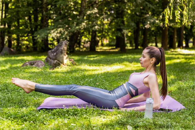 Charming girl doing exercises on the lawn in a park
