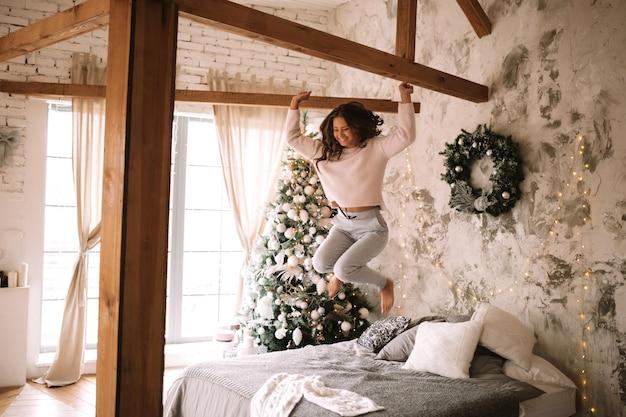 흰색 스웨터와 바지를 입은 매력적인 소녀는 새해 나무가 있는 아늑한 장식된 방에서 회색 담요와 흰색 베개로 침대에 뛰어듭니다. .