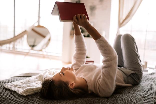 흰색 스웨터와 바지를 입은 매력적인 소녀는 코리 방에서 회색 담요, 흰색 베개, 새해 선물로 침대에 누워 책을 읽습니다. .