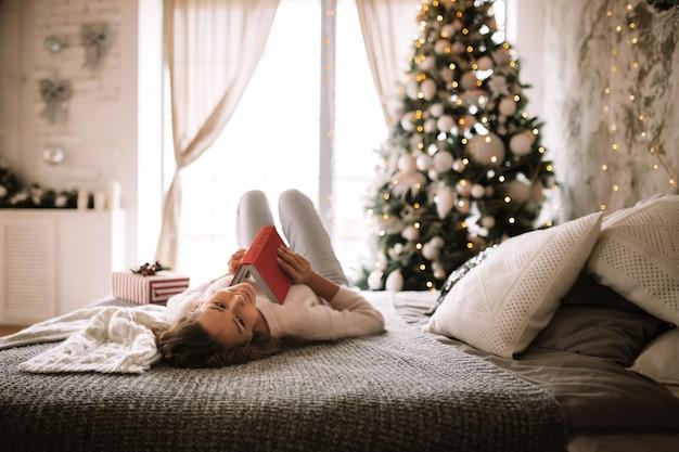 흰색 스웨터와 바지를 입은 매력적인 소녀는 새해 나무가 있는 장식된 방에서 회색 담요, 흰색 베개, 새해 선물로 침대에 누워 책을 읽습니다.