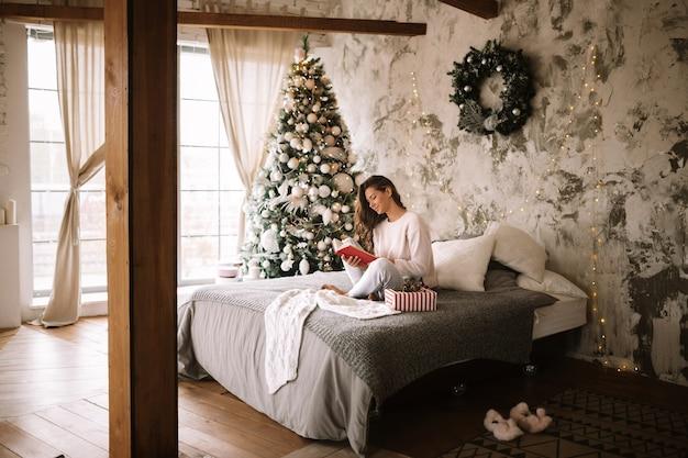 흰색 스웨터와 바지를 입은 매력적인 소녀는 새해 나무가 있는 장식된 방에서 회색 담요, 흰색 베개, 새해 선물로 침대에 앉아 책을 읽습니다. .
