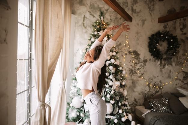 흰 스웨터와 바지를 입은 매력적인 소녀는 창문 앞의 새해 나무 옆에 서서 새해 화환이 있는 아늑한 장식된 방에 몸을 뻗습니다.