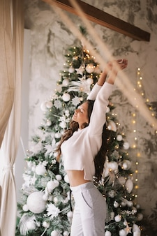 흰 스웨터와 바지를 입은 매력적인 소녀가 창문 앞의 새해 나무 옆에 서서 아늑한 장식된 방에 몸을 뻗습니다.