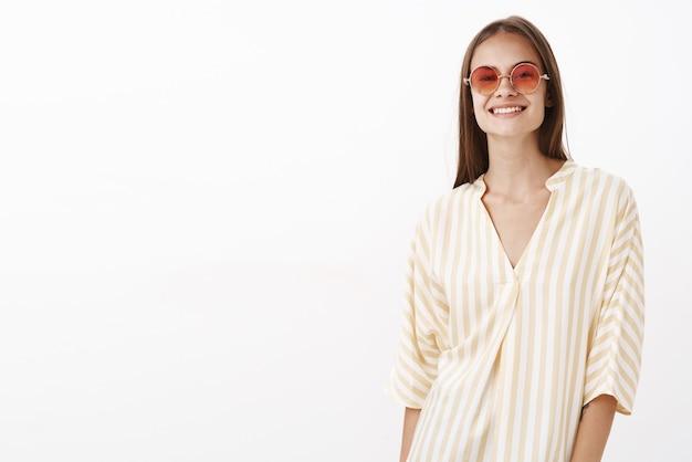 Очаровательная девушка наслаждается теплым солнечным днем, гуляя по пляжу в модной желтой полосатой блузке и солнечных очках, радостно улыбаясь