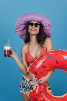 Charming girl in hat and beach dress stands with a cocktail and donut swim ring