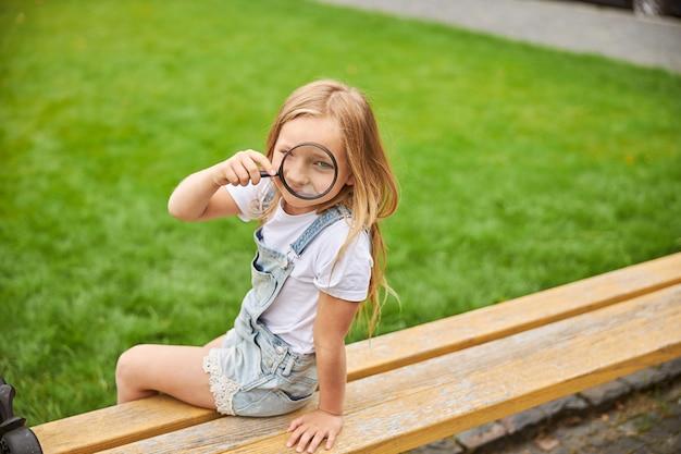 도시 공원에서 나무 벤치에 앉아있는 동안 돋보기를 들고 매력적인 소녀