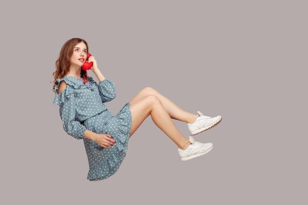 Очаровательная девушка держит телефонную трубку, паря в воздухе и разговаривая