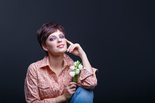 매력적인 여자는 검은 배경에 꽃을 보유