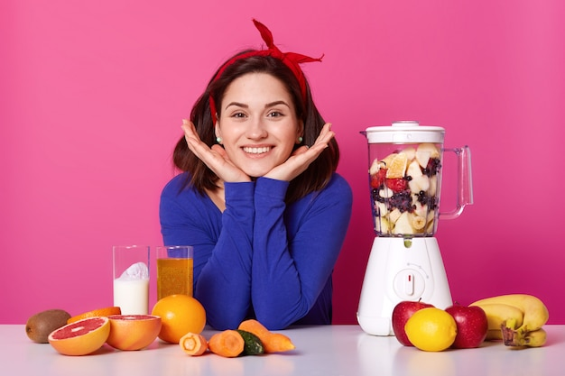 Charming girl, holds hands under chin, wears red headband, blue jumper, uses food processor for making fresh smoothie for breackfast, different fruit and vegetables. dieting, healthy eating concept.