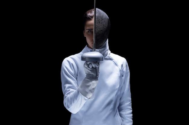 Очаровательная девушка в костюме фехтовальщика позирует на черном фоне. меч разделяет голову на лицо и маску. понятие о ограждении. смешанная техника