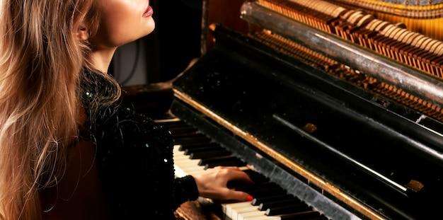 녹색 드레스를 입은 매력적인 소녀는 복고풍 피아노 연주를 즐깁니다. 혼합 매체