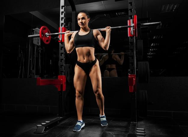체육관에서 매력적인 여자는 바벨로 운동을 수행