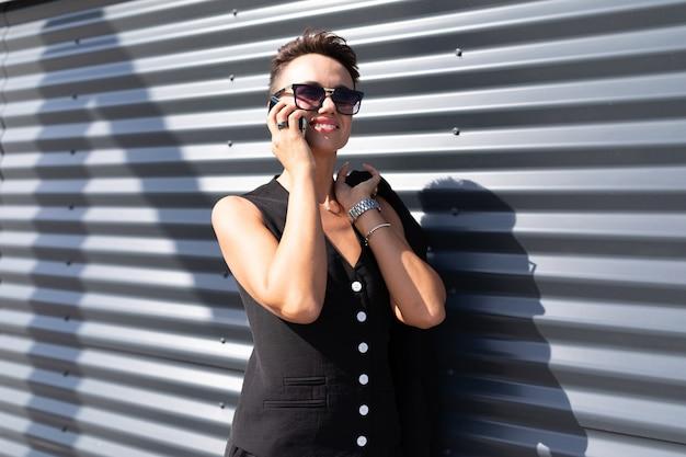 Очаровательная девушка в костюме разговаривает по телефону у стены офисного здания в солнечный летний день