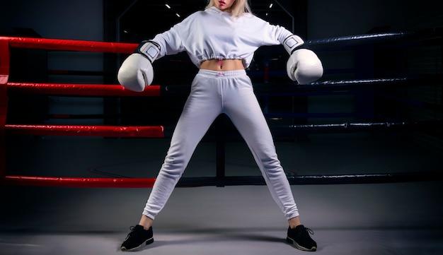 白いスウェットシャツの魅力的な女の子は、ボクシングのリングの背景に巨大な白い手袋でポーズをとる。スポーツ、ジム、スポーツウェア、ボクシングの概念。健康的な生活様式。ミクストメディア