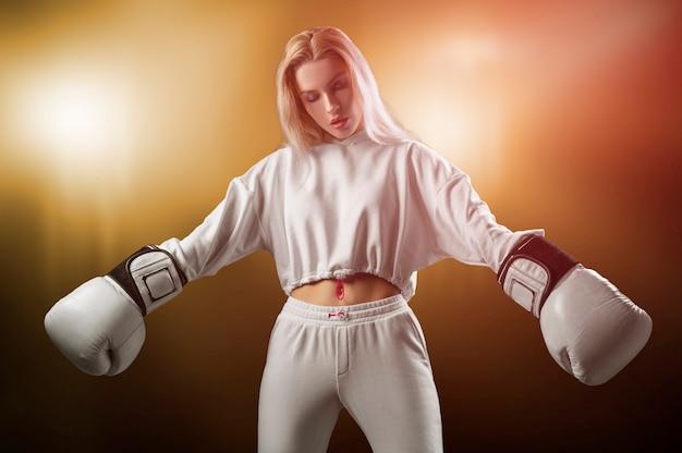 巨大な白い手袋でポーズをとる白いスウェットシャツの魅力的な女の子。スポーツ、ジム、スポーツウェア、ボクシングの概念。健康的な生活様式。ミクストメディア