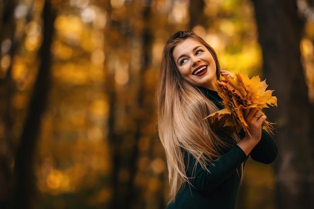 カエデの葉を手に笑顔で持っている秋の公園の魅力的な女の子