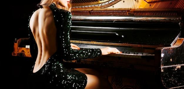 오래 된 독일 피아노 근처 포즈 이브닝 드레스에 매력적인 소녀. 뒷모습. 혼합 매체