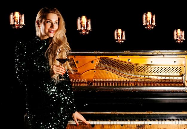 이브닝 드레스에 매력적인 소녀는 피아노에 앉아 와인 한 잔과 함께 카메라에 포즈를 취합니다.