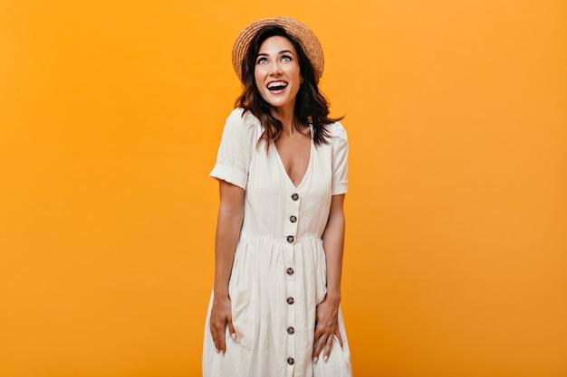 모자와 오렌지 배경에 행복 하 게 포즈 흰 드레스에 매력적인 여자. 카메라에 포즈를 취하는 여름 옷에 물결 모양의 머리를 가진 좋은 분위기에서 행복 한 소녀.