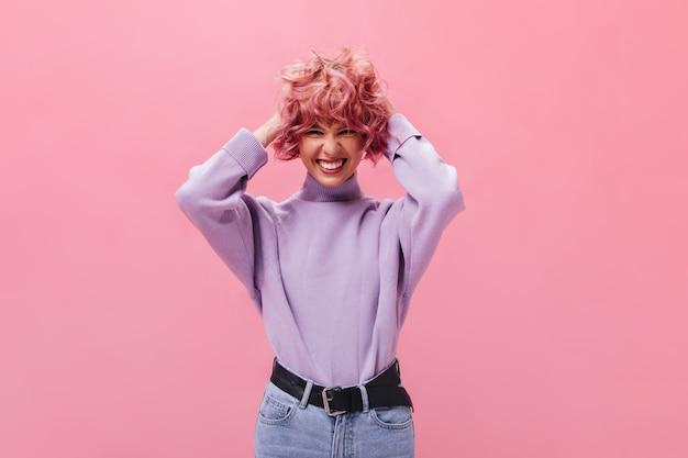 보라색 스웨터를 입은 매력적인 소녀가 분홍 곱슬한 짧은 머리를 헝클어뜨렸습니다.