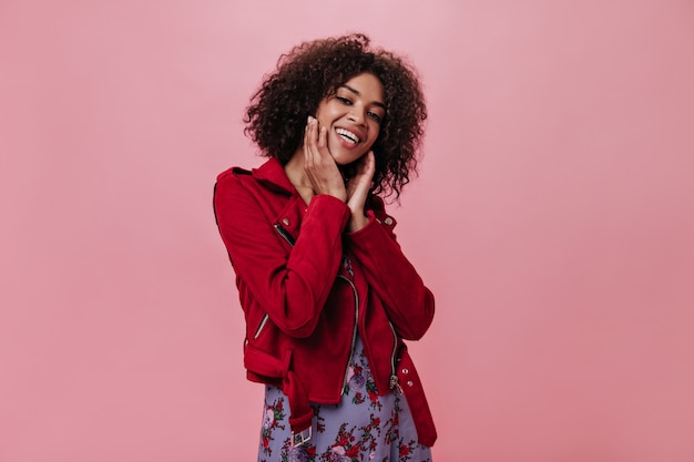 赤いジャケットの魅力的な女の子はピンクの壁に笑う