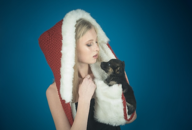 메리 크리스마스와 새해 복 많이 받으세요 강아지와 함께 산타 클로스 모자에 매력적인 소녀