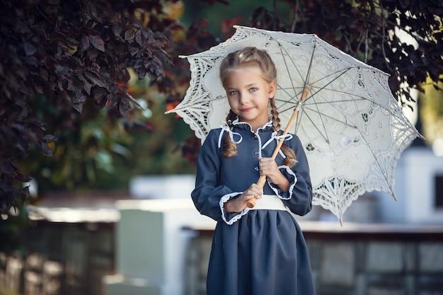制服姿の魅力的な女の子が朝の街を歩く。授業前の美しい若い女子高生