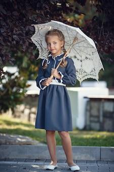 교복을 입은 매력적인 소녀가 아침 도시에서 산책합니다. 수업 전에 아름 다운 젊은여 학생