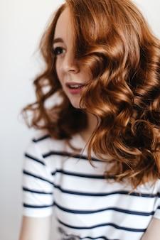 부드럽게 미소로 멀리 찾고 스트라이프 티셔츠에 매력적인 여자. 기쁜 red-haired 젊은 여자의 초상화입니다.