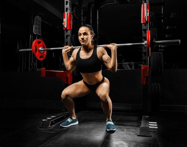체육관에서 매력적인 여자는 바벨과 웅크 리고.