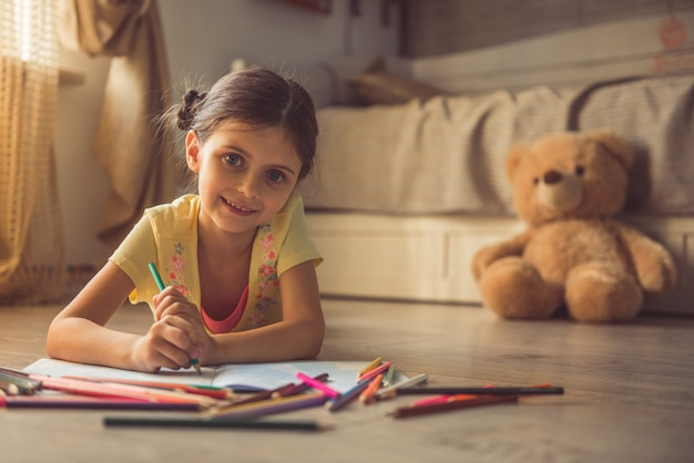 Charming girl is drawing and smiling