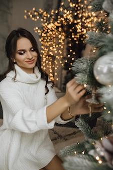 Очаровательная девочка вешает игрушку на елку