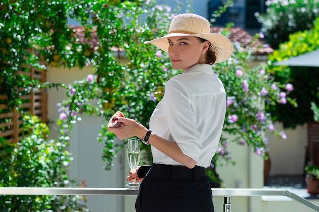 魅力的な女の子がシャンパンと桃のグラスを持って庭に立っています。休暇、旅行、カントリーハウスのコンセプト。ミクストメディア
