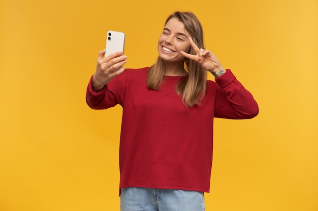 Charming girl keeps mobile phone in her hand, looking on it like making selfie, smiling to it, gives peace gesture