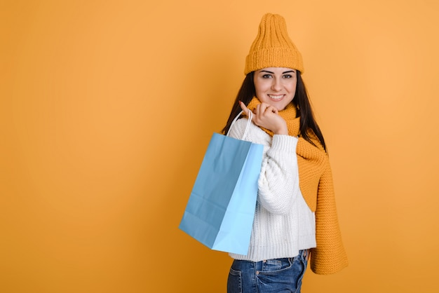 Charming girl in knitted hat and scarf with shopping bags posing in studio