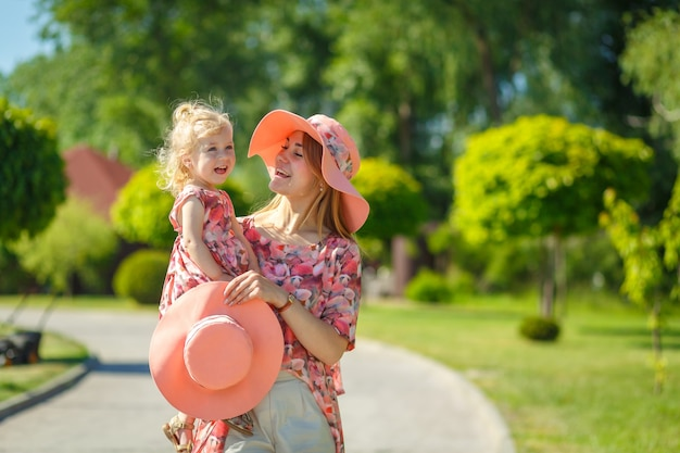 A charming girl in a light summer sundress walks in a green park with her little daughter, holding her in her arms. enjoys warm sunny summer days.