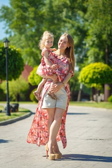 A charming girl in a light summer sundress walks in a green park with her little daughter, holding her in her arms.