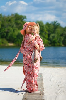 A charming girl in a light summer sundress walks on the sandy beach with her little daughter.