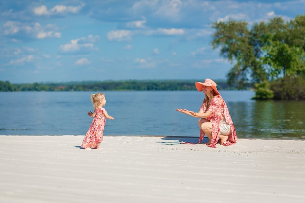 A charming girl in a light summer sundress walks on the sandy beach with her little daughter