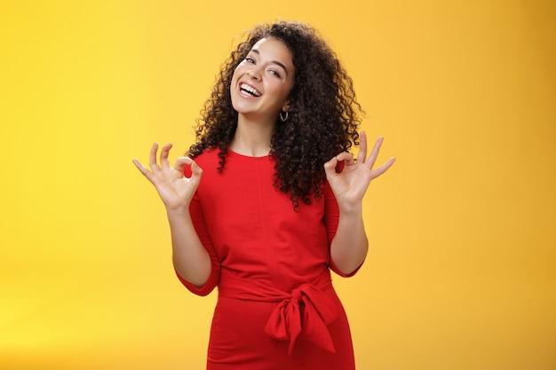 魅力的な女の子は、黄色の背景の上に涼しい場所を承認する広い笑顔で彼氏が大丈夫なジェスチャーを示し、頭を傾けて新しいアパートの家賃を好むように幸せで満足して立っている夢を生きています。