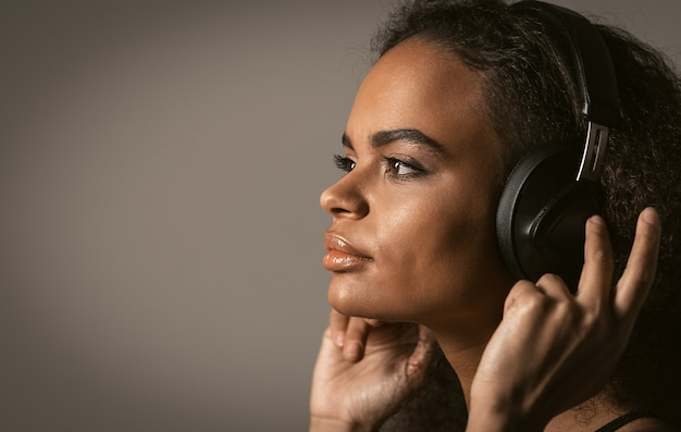 Charming girl looking sideways listening to music wearing headphones holding it with hands, isolated on grey wall