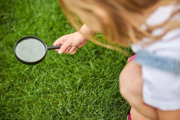 정원에서 푸른 잔디에 잎을 통해 찾고 매력적인 소녀