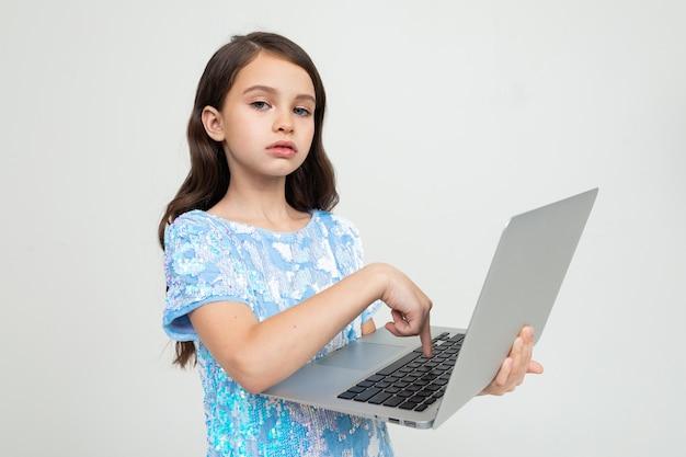 魅力的な女の子が白のラップトップを使用してインターネット経由で教育コースを注文しました
