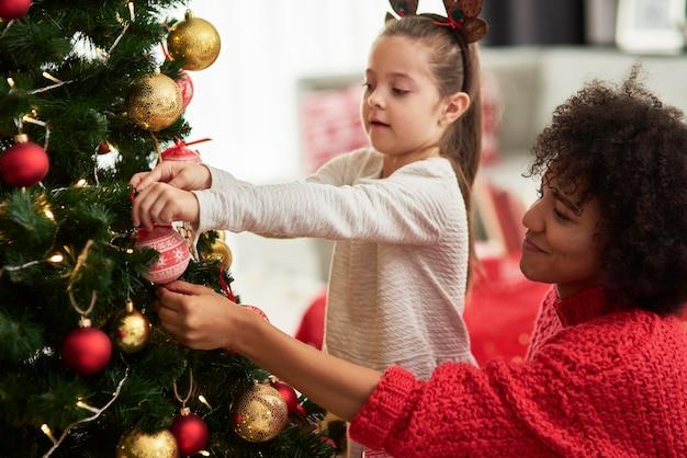 Affascinante ragazza e mamma che decora l'albero di natale