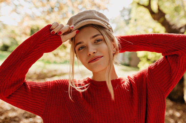 Charming girl in nice light hat and red sweater