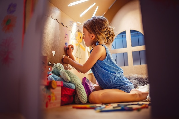 Charming girl playing in toy house