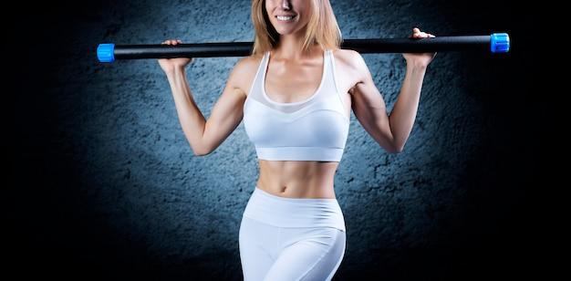 Очаровательная девушка позирует с бодибаром. без имени. понятие фитнеса, бодибилдинга и здорового образа жизни. смешанная техника
