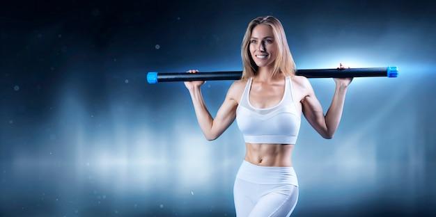 Очаровательная девушка позирует с бодибаром. понятие фитнеса, бодибилдинга и здорового образа жизни. смешанная техника